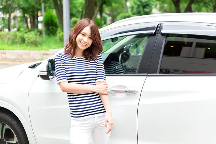 女の人が車の前で写真を取っている所